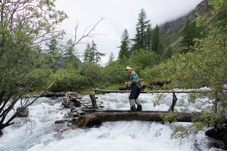 Woman tourist hiking  by pedestrian bridge, through a stormy mountain stream ,  Natural Park in the Belukha Mountain Area, Altai Mountains, Russia