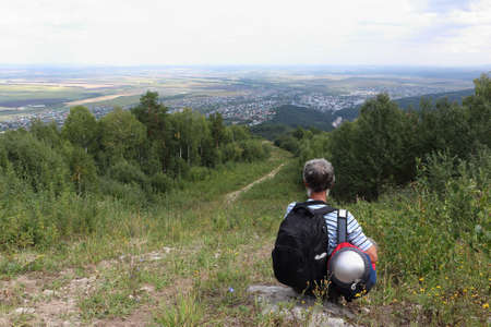 Man with a backpack sitting by the trail on Mount Tserkovka, Belokurikha city, Altai, Russia