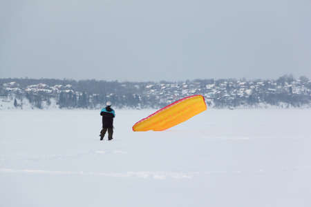 Man training with a kite on a frozen river in the winter, Kama Reservoir, Perm city, Russia