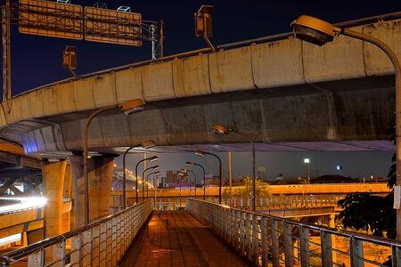 Crossing under the freeway bridge with night illumination , Bangkok, Thailand . photo