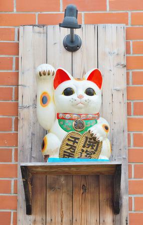 maneki: Maneki Neko cat. on the wall block.Common Japanese sculpture bring good luck to the owner. Stock Photo