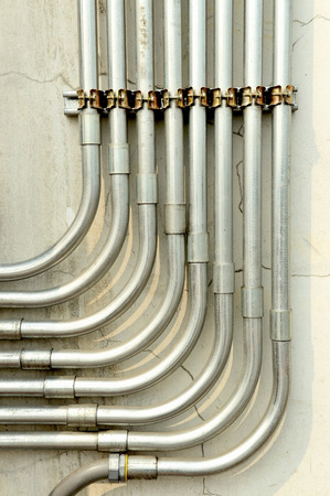 tubing: Aluminum tubing for wire protection lined up on old concrete wall .