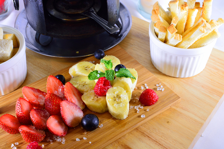 fruits on wood plate for cheese fondue