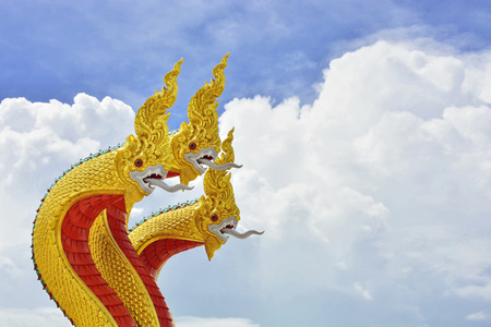 Golden nagas sculpture and beautiful cloud in the sky