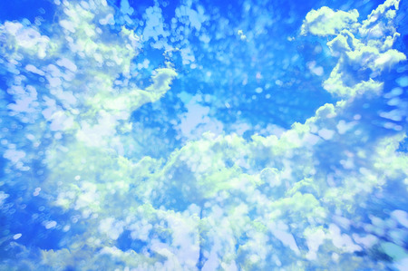 Creative double exposure blue sky with floating clouds blue bokeh splash closeup.
