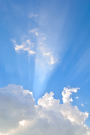 Rays of light coming out of the clouds in the sky . Stock Photo