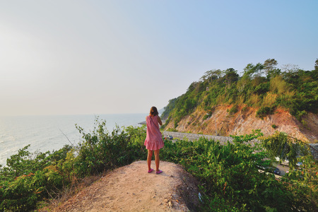 Woman standing shooting mountain road by the sea Standard-Bild