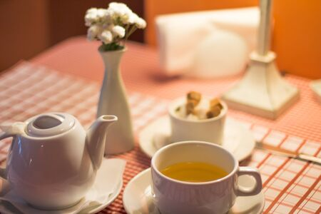 Cup of green tea with teapot andsugar bowl