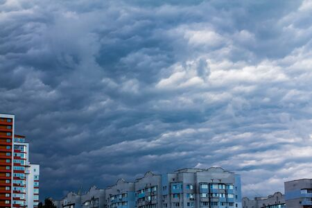 low hanging clouds over the city - the weather before the storm  The stormy moody weather Stock Photo