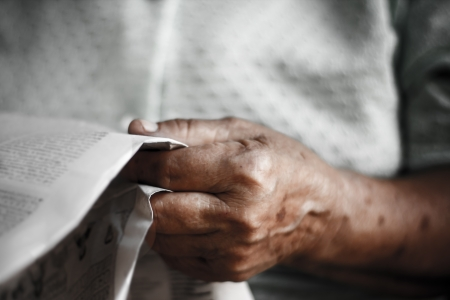 newspaper in the hand of  old woman