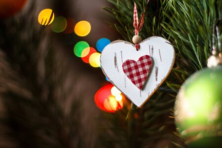 decoration - white wooden heart with fabric red heart inside on the Christmas tree  Valentine Day  Stock Photo