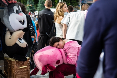 KYIV, UKRAINE - MAY 19  tired man in a pink piggy costume sleeps in the middle of the crowd in the
