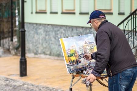 KIEV, UKRAINE - APRIL 14  Elderly artist paints a picture of oil in Andrew Stock Photo - 20737958