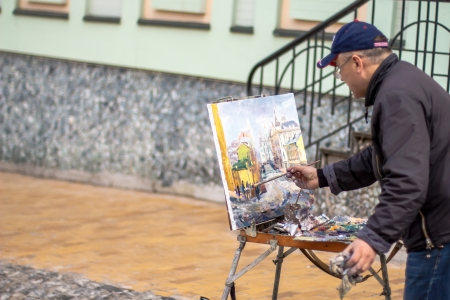 KIEV, UKRAINE - APRIL 14  Elderly artist paints a picture of oil in Andrew