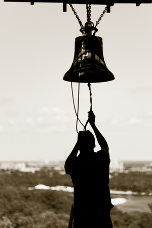 Man rings bell - Memory Church Bell of Memorial to the Victims of Holodomor in Kiev, Ukraine.