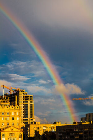 Photo of bright colorful rainbow over city, sun shining in rainy day, beautiful colors phenomenon in dark blue sky, overcast weather, nature landscape in the town, autumn, gh Stock Photo