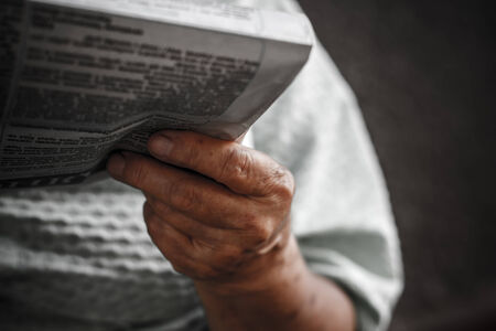 newspaper in the hand of  old woman (blurred russian font)