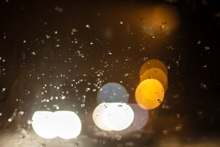 Drops of rain on window with abstract lights. On back plan washed away lights of the torches. Shallow DOF, bokeh Stock Photo