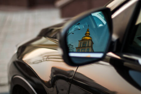 Reflection of the Orthodox Church in the car mirror.