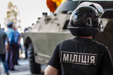 closeup of ukrainian riot policeman wearing protective vest and helmet with armored military vehicle in background. Stock Photo