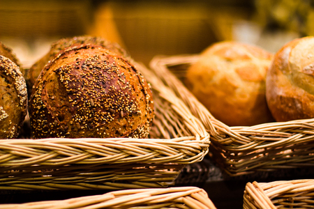 tasty and appetizing buns with sesame seeds in a straw basket