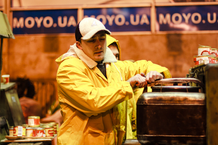 KIEV  KYIV , UKRAINE - DECEMBER 4, 2013  Euromaidan protester prepares on military field kitchen  Unidentified people taking part in anti-goverment protests in Kiev, Ukraine  Editorial