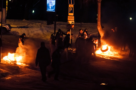 KIEV  KYIV , UKRAINE - JANUARY 26, 2014  Unidentified people taking part in anti-goverment protests in Kiev, Ukraine  Protesters defend barricades and burn tires