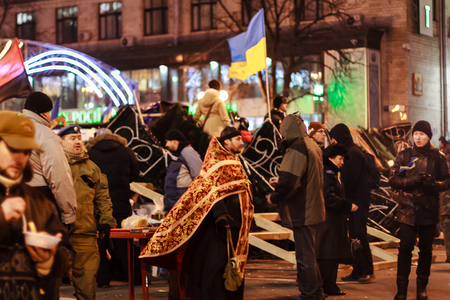 KIEV  KYIV , UKRAINE - DECEMBER 4, 2013  Euromaidan protesters rest  Orthodox priest talks with protesters  Unidentified people taking part in anti-goverment protests in Kiev, Ukraine