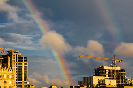 Photo of bright colorful double rainbow over city, sun shining in rainy day, beautiful colors phenomenon in dark blue sky, overcast weather, gh  Crane in dramatic sky Stock Photo