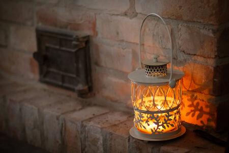 white lantern on a shelf near the fireplace against a brick wall  beautiful Christmas card  Stock Photo