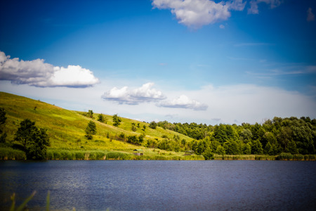 Summer rural landscape with the lake, rolling hills, trees and blue sky. Spring summer background.