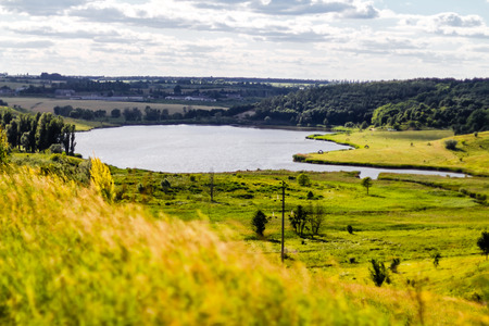 Beautiful lake landscape in ukrainian countryside. Summer background with lake and cloudy sky