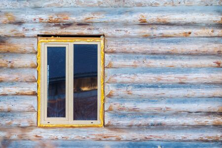 Wooden window in a log Russian hut. The concept of building a house from round timber. Copy space.