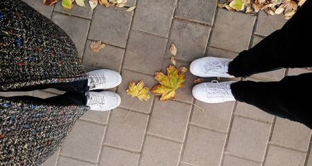 Two pairs of human feet stand on the pavement, keeping a social distance between them. The concept of increasing distance from each other for social distancing to avoid the spread of disease