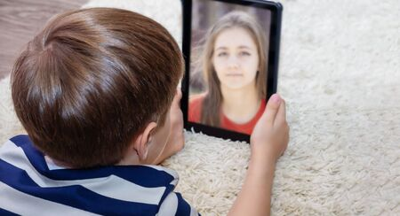 A young person or child who uses a digital tablet to make video calls to friends, family, or a girl. Online communication using a computer webcam that makes a video call