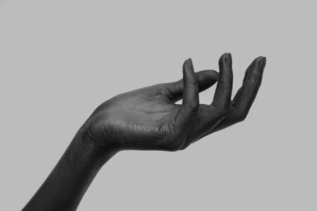 Black female hand holding something invisible, isolated objects on a gray background. Panorama with a copy of the space, black-and-white photo