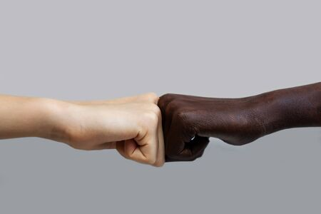 The black African-American hand and the white European hand give a blow to the partnership and cooperation agreement against a grey isolated background.The concept of combating racism