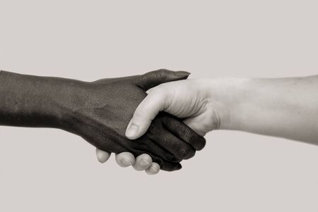 Black and white human hands in joint handshake on an isolated background. The concept of combating racism, friendship and respect between peoples.Selective focus, close-up,black and white photography Zdjęcie Seryjne