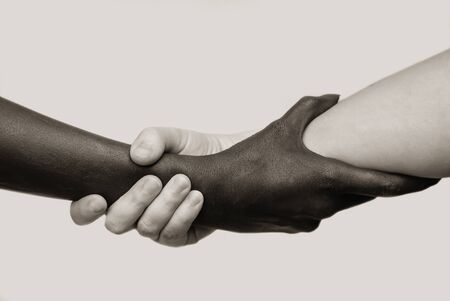 Black-and-white human arms wrapped tightly around each other . The concept of combating racism, friendship and respect .Selective focus, close-up, black and white photography, isolated background