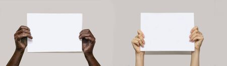Black male hands and white female hands hold a blank sheet of white paper on an isolated gray background. The concept of protest, slogans, the fight against racism. Copy space, banner