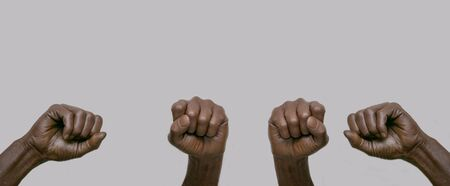 Black African-American human hands with raised fists in the air on a gray isolated background. Close-up, banner, copy space. The concept of protest, violence and struggle