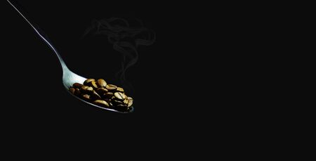 Hot roasted coffee beans on a chrome metal spoon on a black background. Close-up, banner, copy space