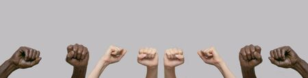 Two pairs of black and two pairs of white human hands, fists raised in the air against a gray isolated background. Close-up, banner, copy space. The concept of protest, violence and struggle,