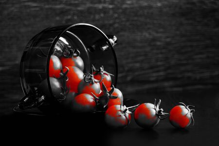 Fresh, red cherry tomatoes spill out of a black transparent glass plate, on a dark background. Selective focus, low key, red highlighting effect