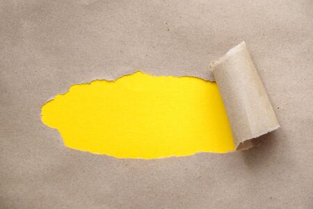 A small hole in the paper with torn sides on a craft background for your text, print, or advertising content. A yellow background is visible through the paper or torn hole. Advertising and the concept of a breakthrough