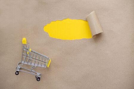 Shopping cart next to a small hole in the paper with torn sides on a brown background for your text, print, or advertising content. The yellow background is visible through the hole. Standard-Bild