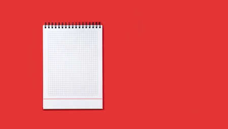 Open school notebook with lined white sheets in a check on a red background, the concept of back to school , modern primary education. The view from the top, flat lay, copy space