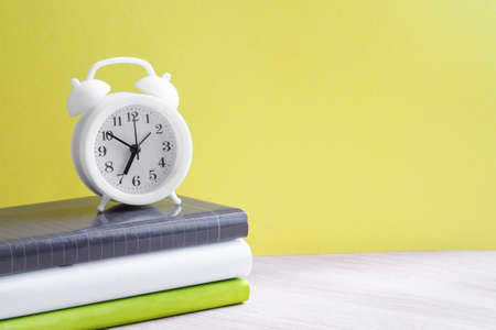 A white alarm clock stands on a stack of three books with colorful spines on the table. Yellow background, close-up, copy space. Back to school concept Standard-Bild