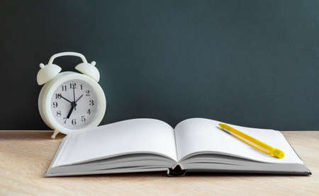 A white alarm clock stands next to an open book with white lined pages and a yellow pencil. Items lie on the background of the school Board. Let's go back to the concept of a school,a copy space