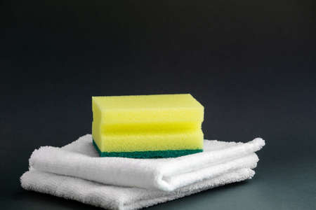 Yellow foam sponge for washing dishes and two white household rags for cleaning on a dark background. Concept of world cleanliness day. Close-up, copyspace.